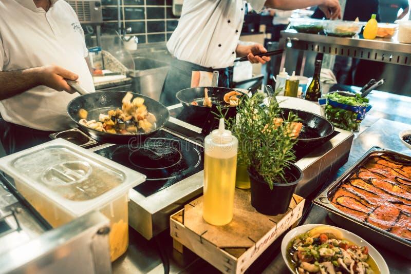 Vari ingredienti freschi sulla stufa di una cucina commerciale immagine stock libera da diritti