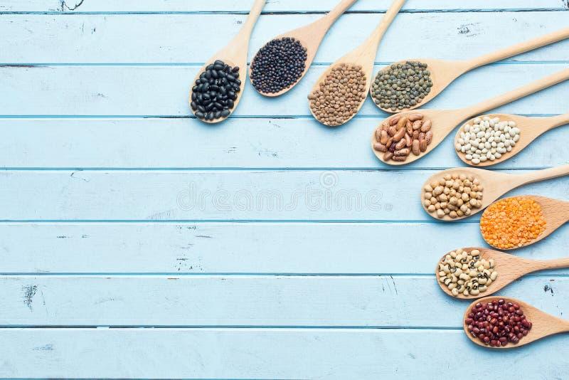 Vari legumi secchi in cucchiai di legno fotografie stock libere da diritti
