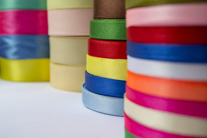 Vari nastri colorati sulla tavola bianca con fondo confuso C immagini stock