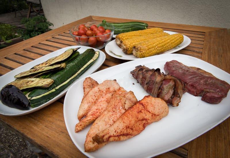 Vari piatti deliziosi pronti in un fumatore del barbecue che sta su una tavola di legno fotografia stock