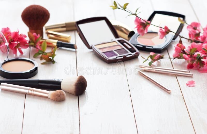 Vari prodotti cosmetici per trucco con i fiori rosa su un fondo di legno bianco con lo spazio della copia immagine stock