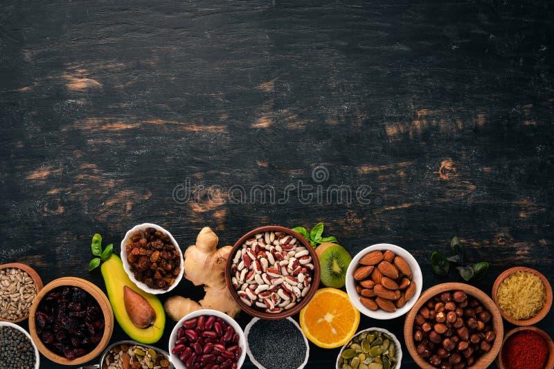 Vari superfoods Frutti, dadi, fagioli, frutta e verdure secchi Su un fondo di legno nero fotografie stock libere da diritti