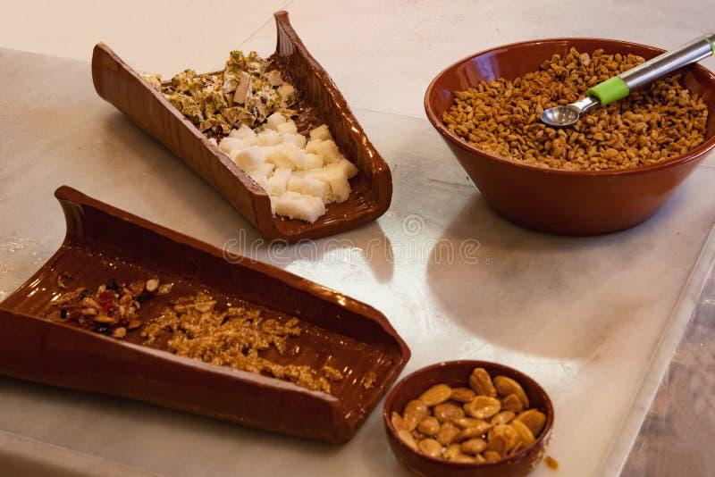 Vari tipi di dolce fatti dal nougat matto, bianco e marrone in ciotole marroni che hanno state appena fresco pronto in nougat immagini stock