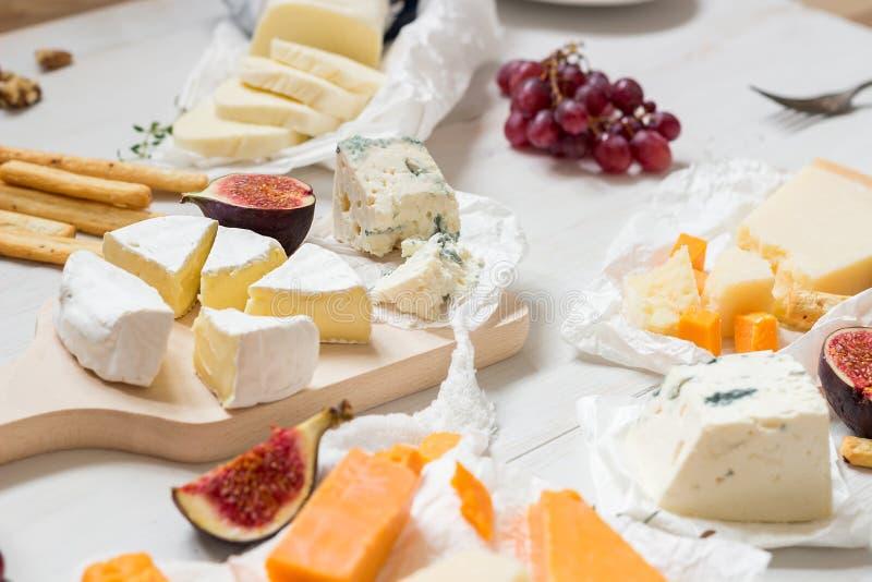 Vari tipi di formaggi con i frutti sulla tavola bianca di legno Fuoco selettivo immagine stock libera da diritti