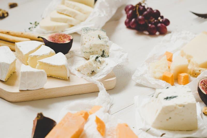 Vari tipi di formaggi con i frutti sulla tavola bianca di legno Fuoco selettivo fotografia stock