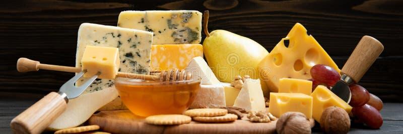 Vari tipi di formaggi su una tavola rustica fotografia stock