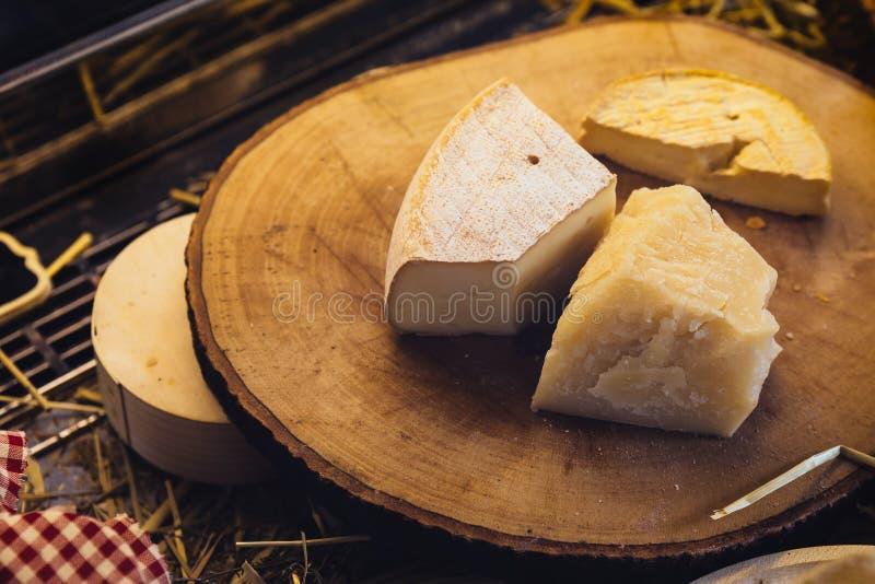 Vari tipi di formaggi sul tagliere di legno rustico fotografia stock