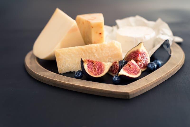 vari tipi di formaggi sulla tavola di legno rustica, formaggio di capra, chevre, padana di grana, fico, mirtillo fotografia stock