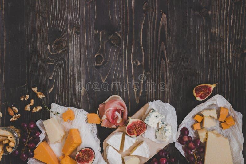 Vari tipi di formaggio con i frutti e di spuntini sulla tavola scura di legno con lo spazio della copia fotografia stock