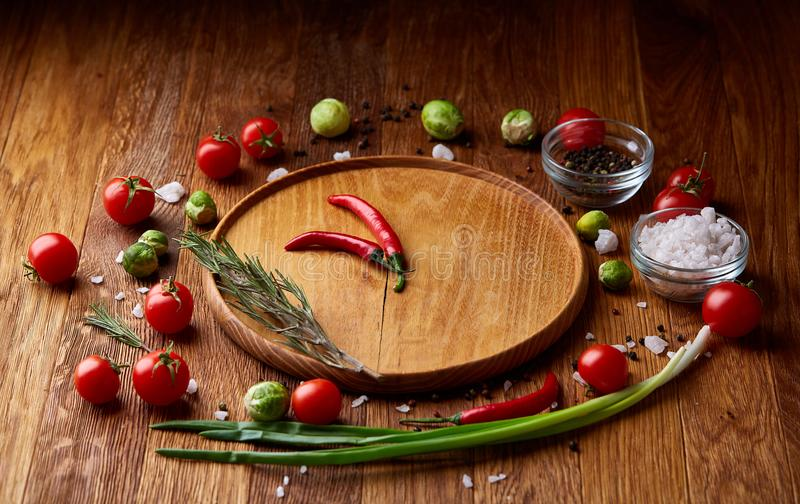 Vari verdure, condimento e spicies intorno al piatto in bianco su fondo di legno rustico, vista superiore immagine stock