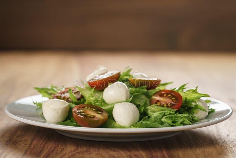 Variação da salada de Caprese com tomates do kumato e folhas dos frillies fotos de stock royalty free