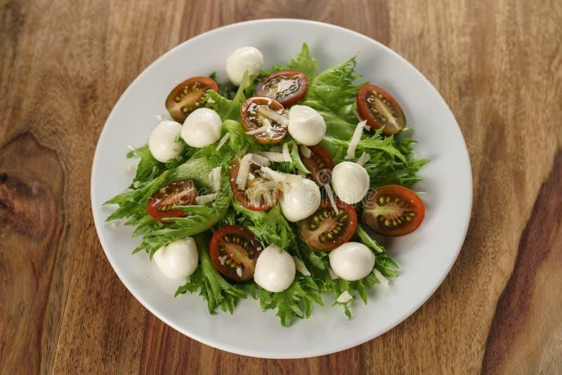Variação da salada de Caprese com tomates do kumato e folhas dos frillies foto de stock