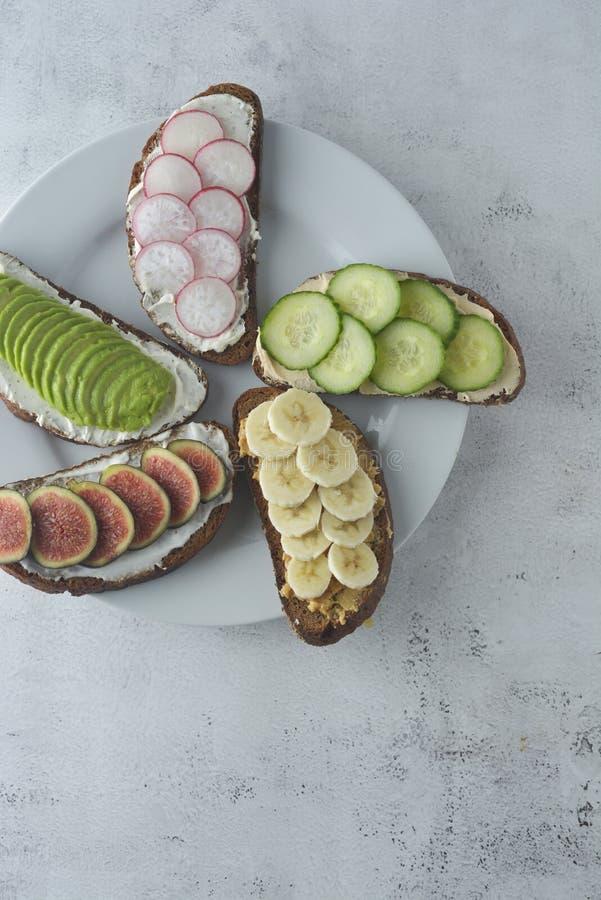 Variação de sanduíches saudáveis do café da manhã com abacate, pepino, fruto do figo, banana, queijo creme e pão wholegrain fotografia de stock royalty free