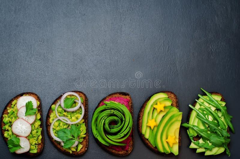 Variação de sanduíches saudáveis do café da manhã do centeio com abacate e t fotos de stock royalty free