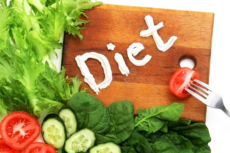 Varia verdura presentata vicino al tagliere con la dieta di parola, scritta panna acida Sul bordo è una forcella Dieta di simbolo fotografie stock libere da diritti