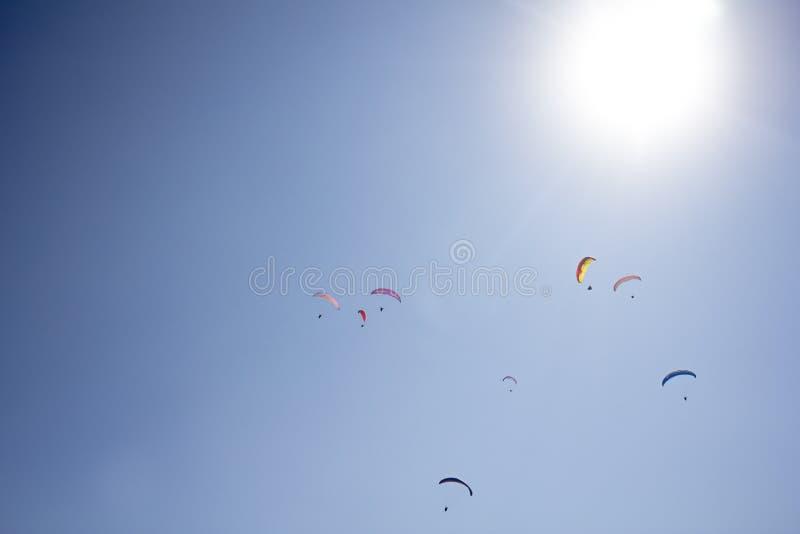 Varias alas flexibles en los paracaídas coloridos en un cielo azul claro con un sol brillante fotos de archivo
