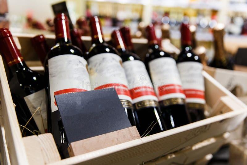 Varias botellas de vino con las etiquetas vacías en cajas de madera foto de archivo
