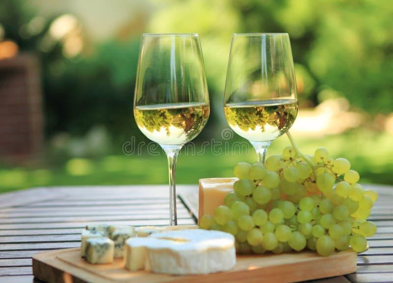 Varias clases de queso y de vino blanco imagen de archivo