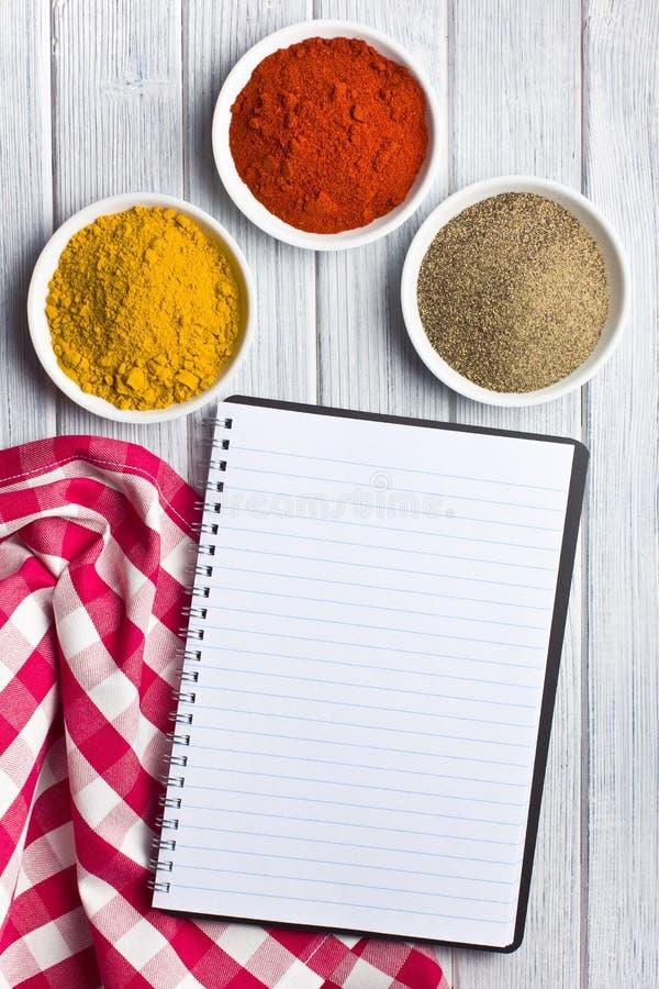 Varias especias coloreadas con el libro en blanco de la receta imagen de archivo libre de regalías