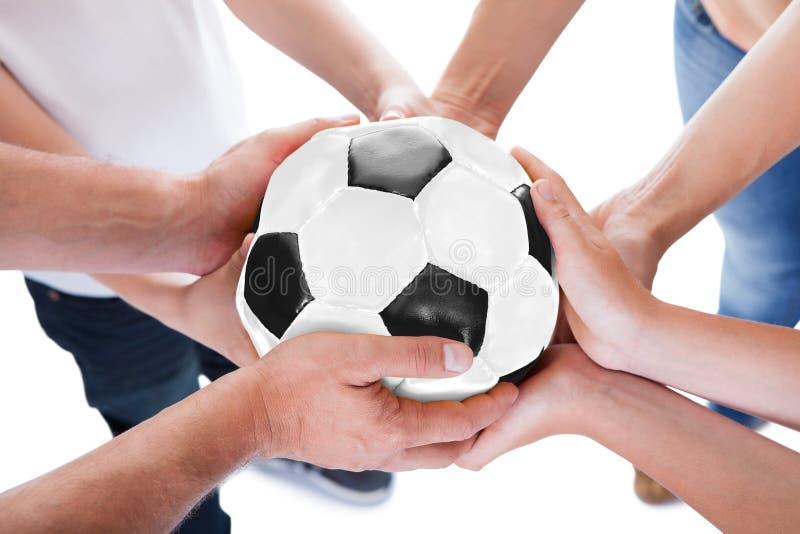 Varias manos que ligan el balón de fútbol fotografía de archivo libre de regalías
