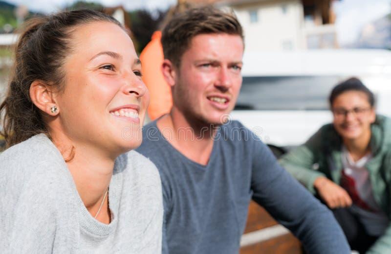 Varias personas masculinas y femeninas jovenes que se sientan en un banco y una sonrisa imagen de archivo