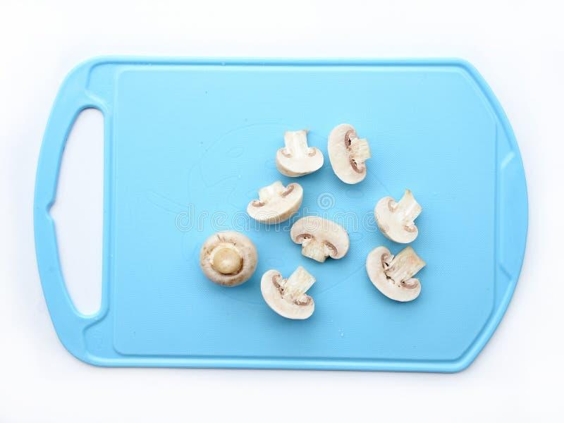 Varias setas cortadas del champiñón en la placa azul imagen de archivo libre de regalías