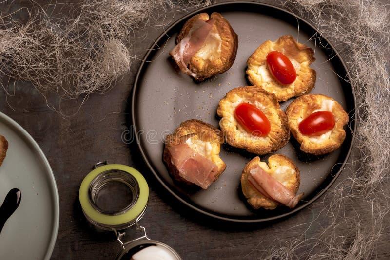 Varias tazas de la pasta de hojaldre rellenas por el queso con los tomates y el jamón foto de archivo libre de regalías