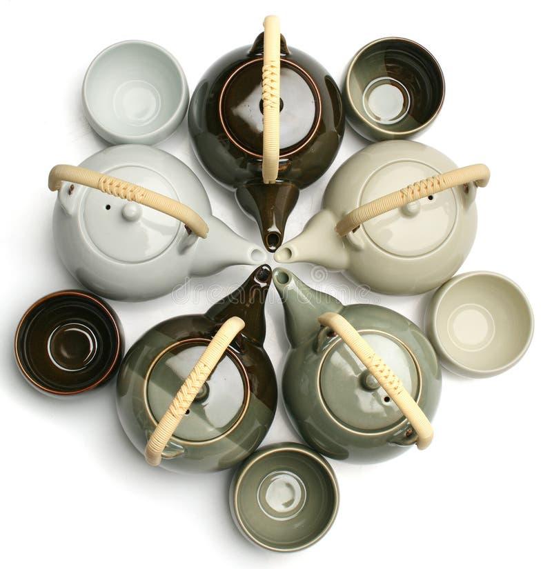 Varias teteras y tazas de té sobre blanco imagenes de archivo