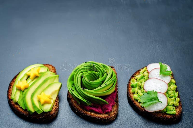 Variatie van de gezonde sandwiches van het roggeontbijt met avocado en t stock afbeelding