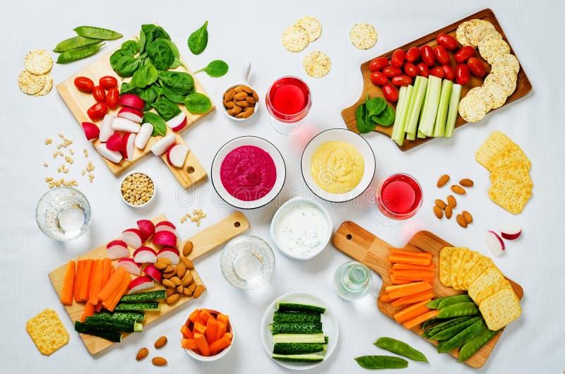 Variatie van gezonde veganistsnacks Groenten, crackers, onderdompeling en hummus stock foto