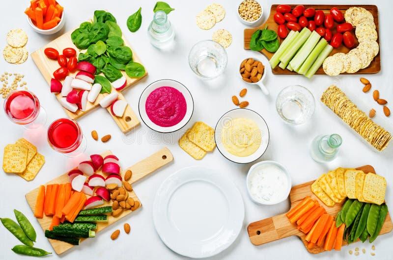 Variatie van gezonde veganistsnacks Groenten, crackers, onderdompeling en hummus royalty-vrije stock afbeelding