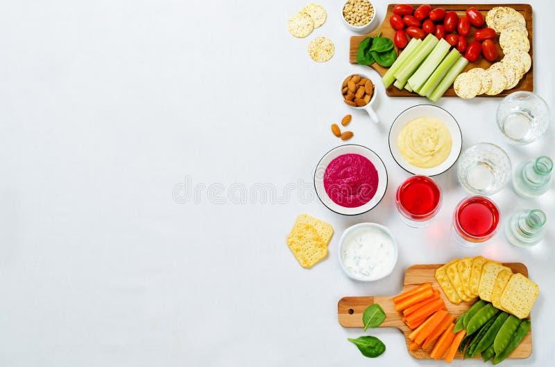 Variatie van gezonde veganistsnacks Groenten, crackers, onderdompeling en hummus royalty-vrije stock foto