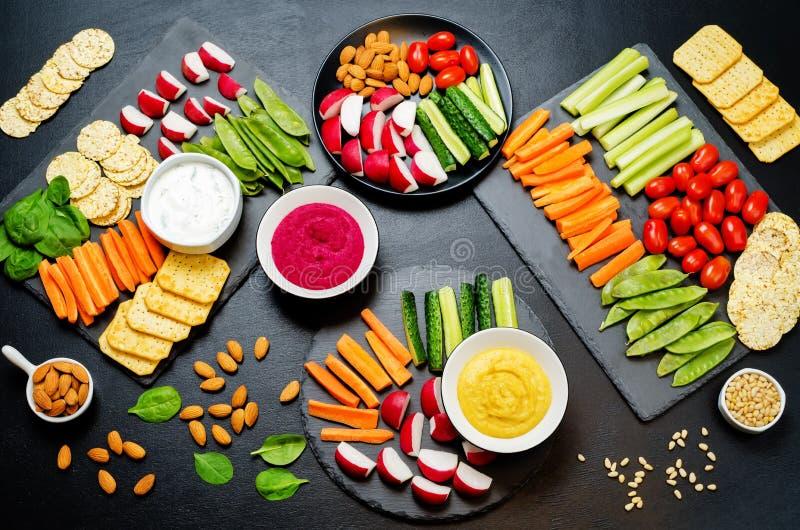 Variatie van gezonde veganistsnacks Groenten, crackers, onderdompeling en hummus royalty-vrije stock afbeeldingen