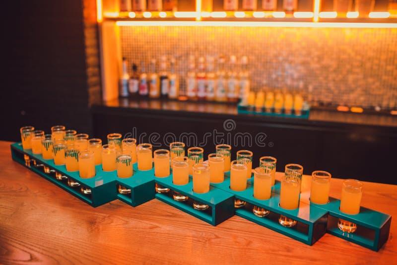 Variatie van harde alcoholische die schoten op barteller worden gediend Onduidelijk beeldflessen op achtergrond royalty-vrije stock fotografie