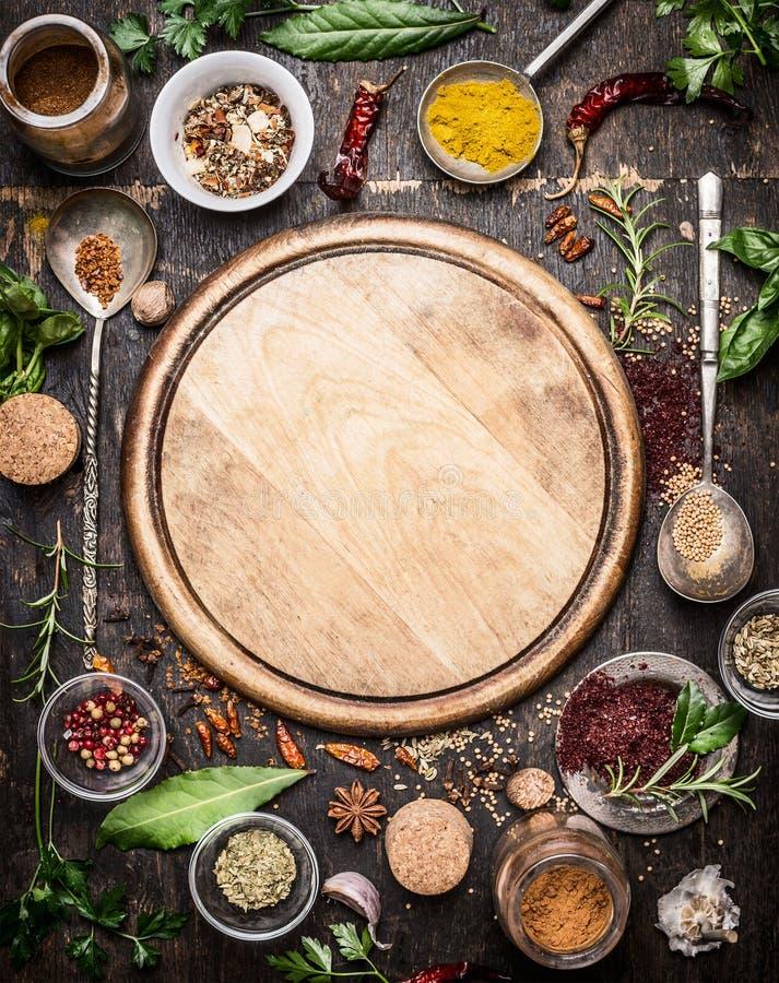 Variation av örter och kryddor runt om tom skärbräda på lantlig träbakgrund, bästa sikt royaltyfri bild