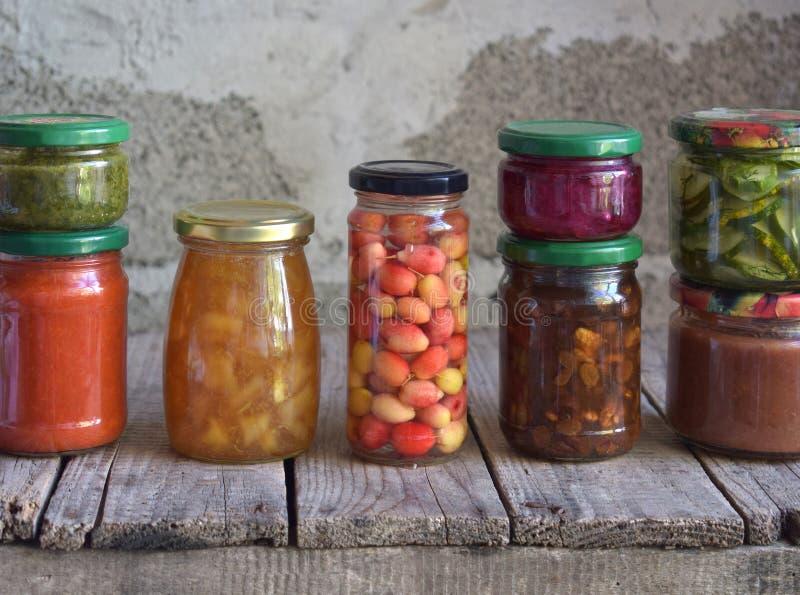 Variation av bevarad mat i exponeringsglaskrus - knipor, driftstopp, marmelad, såser, ketchup Bevara grönsaker och frukter jäst royaltyfria bilder