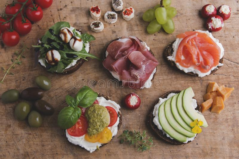 Variation av canape med laxen, prosciutto, avokado, mozzarella, tomat, pesto, oliv, gräddost Blandning av olik mellanmål och appe royaltyfri foto