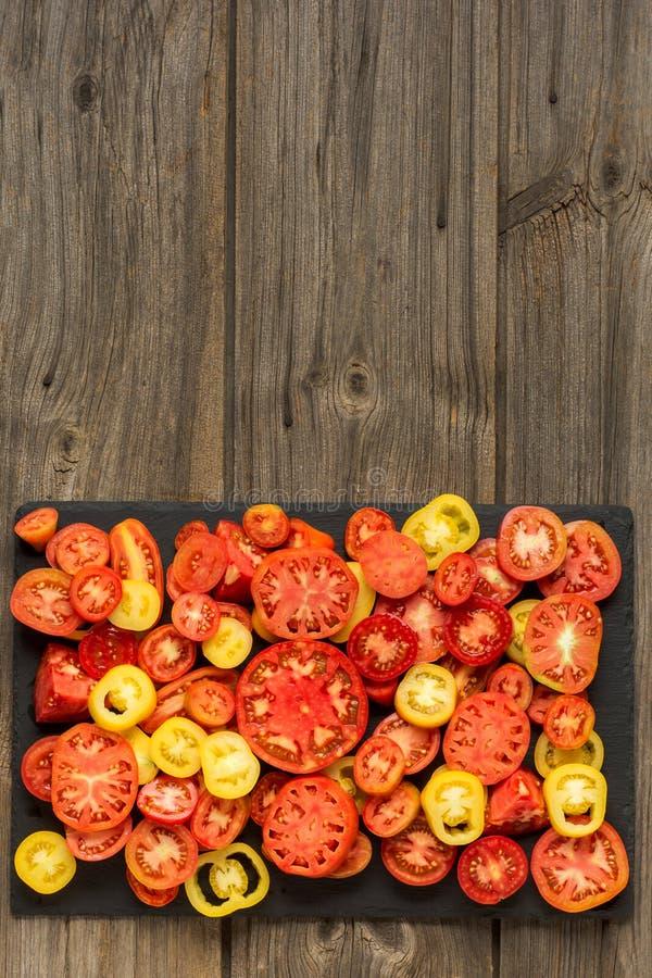 Variation av den mogna nya organiska arbeta i trädgården sorten och färger för tomater olika med sidor för vattenfläck och basili arkivfoto