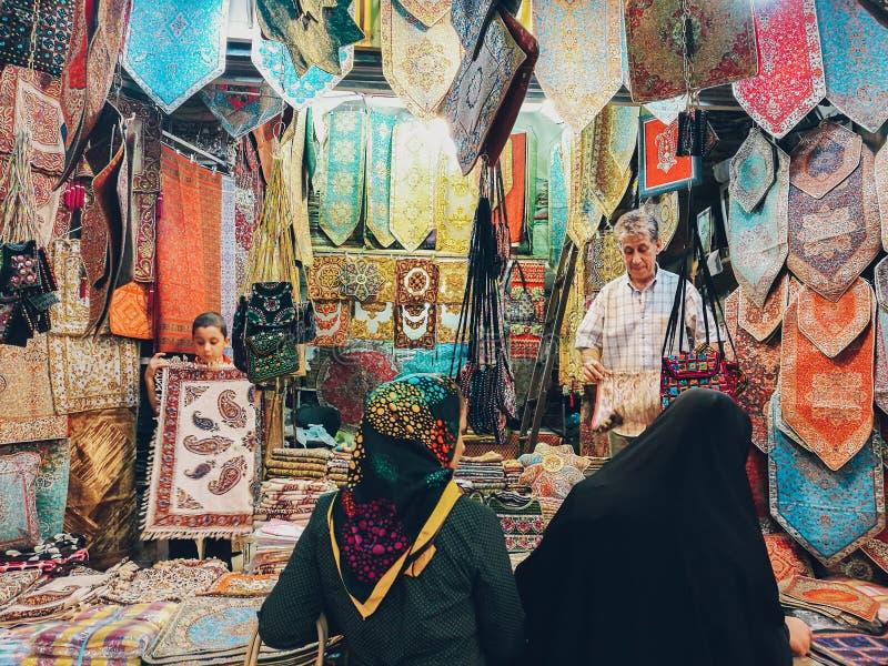 Variation av färgrika filtar, gobelänger och dampåsar som är till salu på den Vakil basaren Shiraz Iran arkivbilder