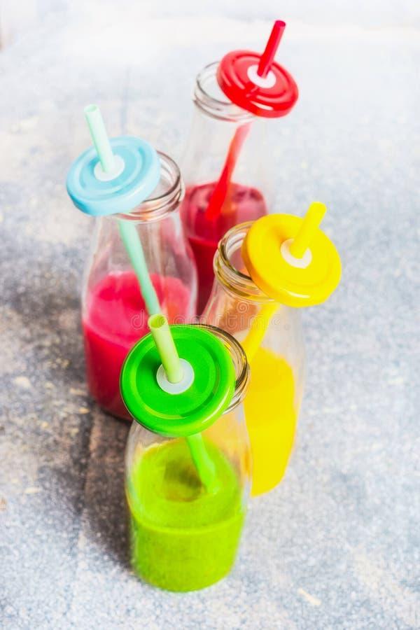 Variation av färgrika smoothies i flaskor med att dricka sugrör arkivfoto