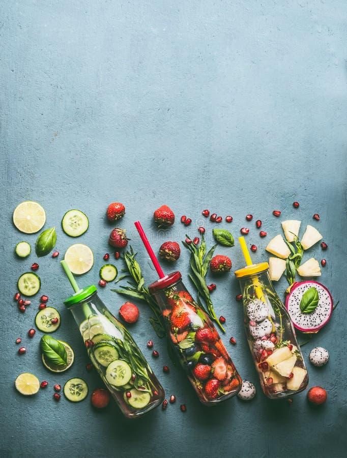 Variation av färgrikt ingett vatten i flaskor med fruktbär, gurkan, örter och drinksugrör med ingredienser på tabellen, överkant arkivbild