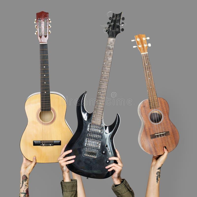 Variation av händer som rymmer gitarrer arkivbilder