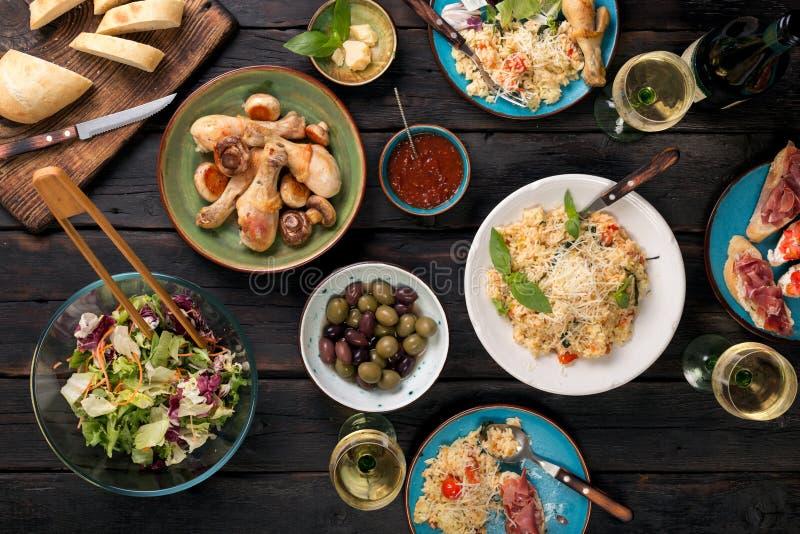 Variation av italiensk mat med vin på den mörka trätabellen arkivfoto