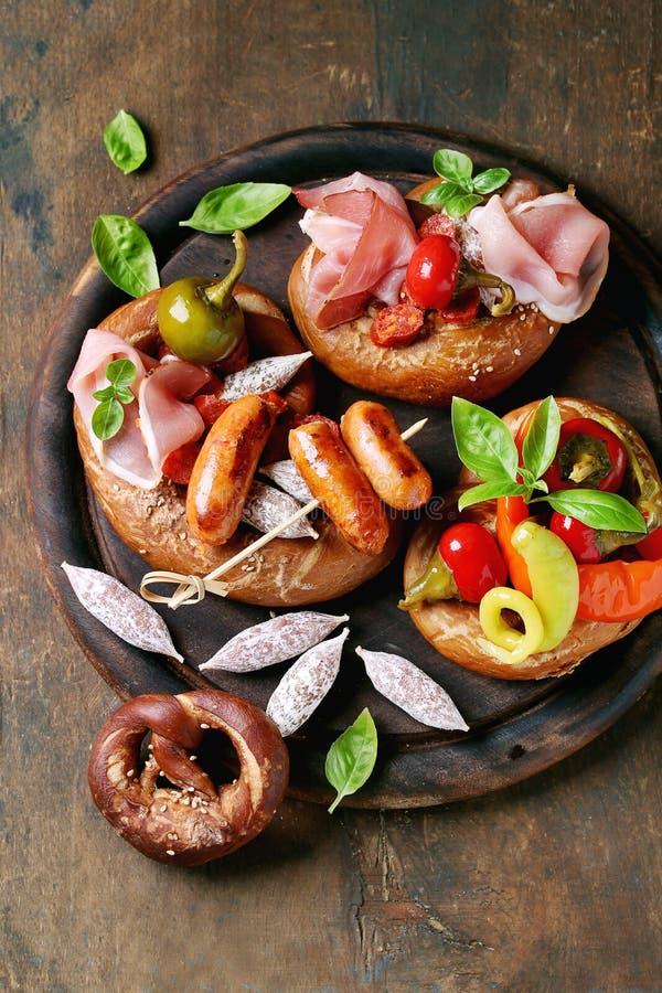 Variation av köttmellanmål i kringlor royaltyfri foto