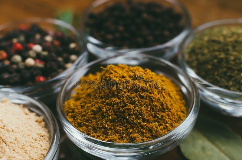 Variation av kryddor i runda exponeringsglasbunkar - jordningsingef?ra, flygturer-suneli, kari, svartpeppar och blandning royaltyfria bilder
