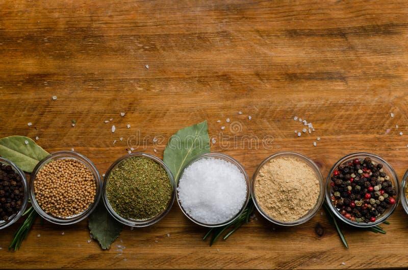 Variation av kryddor i runda exponeringsglasbunkar - jordningsingef?ra, flygturer-suneli, kari, svartpeppar och en blandning royaltyfri bild