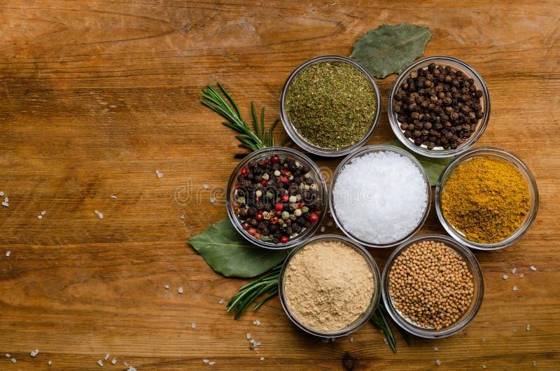 Variation av kryddor i runda exponeringsglasbunkar - jordningsingef?ra, flygturer-suneli, kari, svartpeppar och en blandning arkivbild