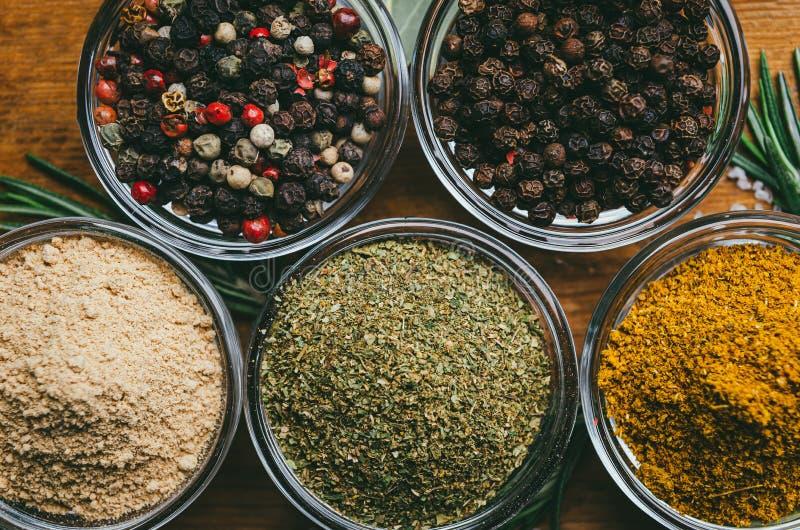 Variation av kryddor i runda exponeringsglasbunkar - jordningsingef?ra, flygturer-suneli, kari, svartpeppar och en blandning royaltyfri fotografi