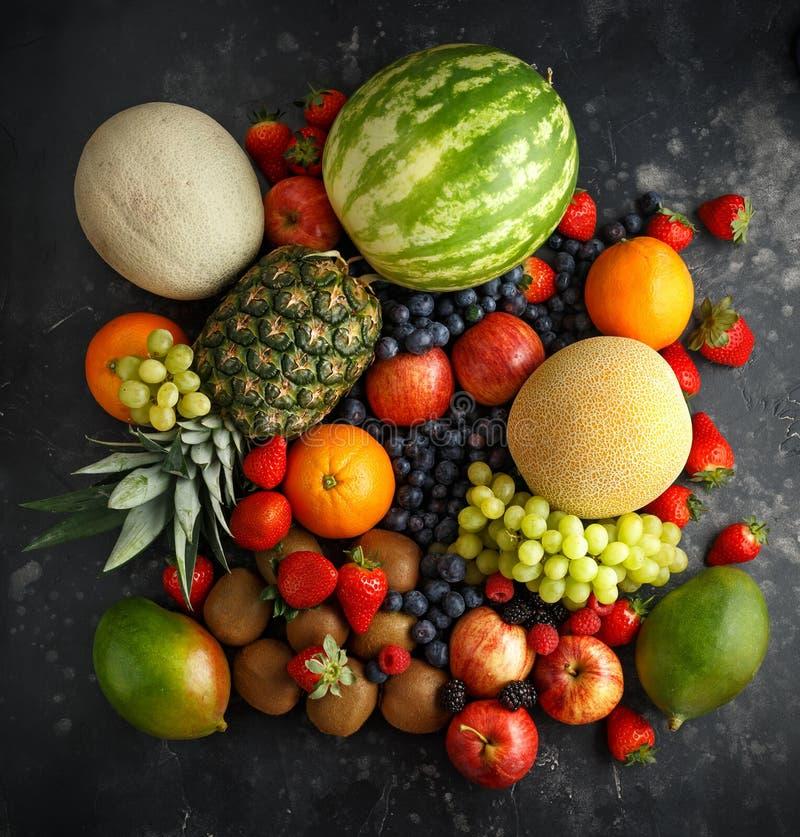 Variation av nya frukter och bär på mörk bakgrund: cantaloupmelon melon, vattenmelon, blåbär, apelsiner, äpple royaltyfri bild