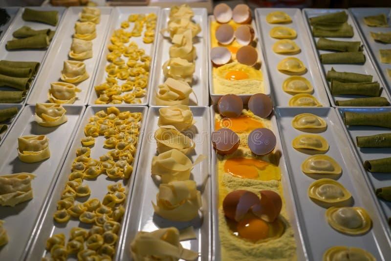 Variation av nya pastatyper ställer ut för matställe inklusive pappardelle, raviolit, etc. på den vita rektangelplattan på natten arkivfoton
